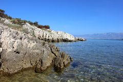 Rocky wild seashore with transparent water Royalty Free Stock Photos