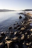 Rocky Winter Shoreline on Lake Pend Oreille Idaho. Vertical photo of Rocky Winter Shoreline on Lake Pend Oreille Idaho with mountains in background and traces of Stock Photos