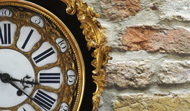 Rococo clock. Black and gold rococo clock against pastel brick wall royalty free stock photography
