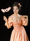 Rococo woman in historical costume with crinoline. Stylized rococo portrait of beautiful brunette woman in historical costume with crinoline and mask. Low key Stock Photo