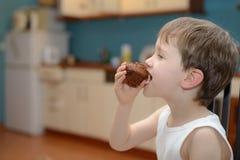 4 roczniaka chłopiec je czekoladowy słodka bułeczka Obraz Stock