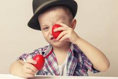 4 roczniaka chłopiec w kapeluszowym i koszulowym mieniu wręcza czerwonych Wielkanocnych jajka, Obraz Royalty Free