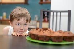 4 roczniaka chłopiec hungrily patrzeje czekoladowego tort Obrazy Royalty Free