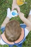 2 roczniaka chłopiec je jogurtu obsiadanie na trawie Obraz Stock