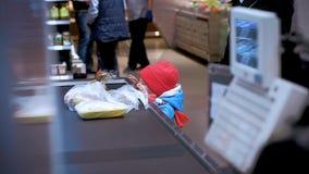 Roczniaka dziecka 3 stojaka obok supermarketa kasjera i spojrzenia przy towarami zdjęcie wideo