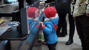Roczniaka dziecka 3 stojaka obok supermarketa kasjera i spojrzenia przy towarami zbiory