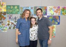 11 roczniaka dziewczyna z rodzicami pozuje przed liści drukami Zdjęcia Stock