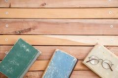Roczników szkła i stare książki na drewnianym tle Odgórny widok zdjęcie stock