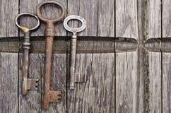 Roczników klucze na starym drewnianym tle Zakończenie Trzy starego, wieśniaków klucze na stole Obraz Stock