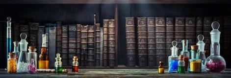 Roczników lekarstwa w małych butelkach na drewnianego biurka i starej książki tle Stary medyczny, chemia i apteka historii pojęci fotografia royalty free