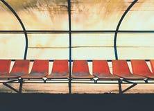 Roczników plastikowi siedzenia na plenerowej stadium graczów ławce, krzesła z przetartą farbą pod dachem Obraz Royalty Free