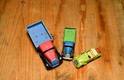 Roczników samochodów zabawkarskiej ciężarówki ciężarowy i odwracalny samochód na brown drewnianym tle Retro zabawki dla chłopiec  Fotografia Royalty Free