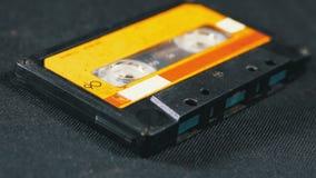 Rocznik żółta audio kaseta wiruje na czarnym tle zbiory wideo