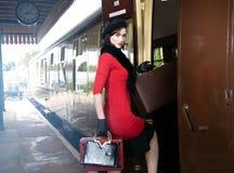 Rocznik atrakcyjna kobieta jest ubranym czerwień smokingowego i czarnego beret z walizkami na platformie dworzec zdjęcia royalty free