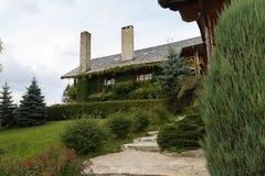 Rocznik beli drewniany dom zakrywający zielonym bluszczem Wiejski dom na wsi z kominem, chałupa, zakrywająca z bluszczem, herbage Zdjęcia Royalty Free