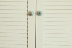 rocznik biała szafa z ozdobnymi rękojeściami na drzwiach wewnętrzny wystroju tło zdjęcie royalty free