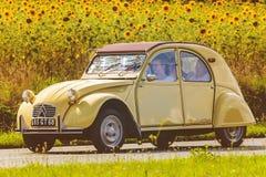 Rocznik Citroen 2CV przed polem z kwitnącymi słonecznikami Zdjęcia Stock