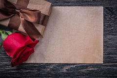 Rocznik czerwieni róży teraźniejszości papierowy pudełko na drewnianej desce Fotografia Stock