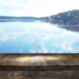 Rocznik drewnianej deski stół przed marzycielskim i abstrakcjonistycznym lasowym jeziorem Fotografia Stock