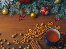 Rocznik filiżanka gorąca herbata z krakers na drewnianym tle dekorował z sosną Zdjęcie Stock