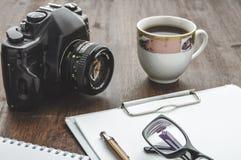 Rocznik filiżanka na drewno stole i kamera Obrazy Stock