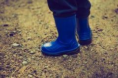 Rocznik fotografia małe dziecko iść na piechotę w podeszczowych butach Zdjęcia Stock