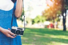 Rocznik jesieni fotografia z dziewczyny pozycją w parku z starą kamerą Zdjęcie Stock