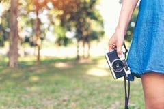 Rocznik jesieni fotografia z dziewczyny pozycją w parku z starą kamerą Zdjęcia Stock