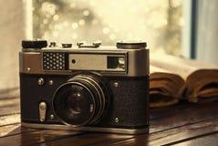 Rocznik kamera i stara książka na stole Obrazy Stock