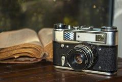 Rocznik kamera i stara książka na stole Obrazy Royalty Free