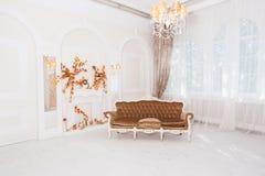 Rocznik kanapa w dużej białej sala z kolumnami i łukami zdjęcie stock