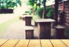 Rocznik, miękkiej ostrości drewniany stół z plamy sklep z kawą tłem Zdjęcia Stock