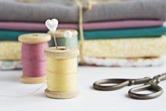 Rocznik nici cewy, nożyce, bawełniane tkaniny i szpilki, obrazy stock