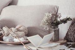 Rocznik nici na wygodnej kanapie z i Otwiera książkę dla czytać zdjęcie stock