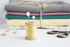 Rocznik niciana cewa, szpilki, nożyce i bawełniane tkaniny, zdjęcia royalty free