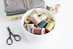 Rocznik niciane cewy, nożyce i bawełniane tkaniny, fotografia stock