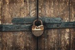 Rocznik ośniedziała kłódka na starych wietrzeć drewnianych bramach obraz stock