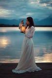 Rocznik panna młoda na jeziornym molu z lampionem Zdjęcie Stock