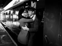 Rocznik pary obejmowanie i śmiać się na staci kolejowej platformie jako pociąg przyjeżdżamy zdjęcie royalty free