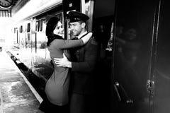 Rocznik pary obejmowanie i śmiać się na staci kolejowej platformie jako pociąg przyjeżdżamy obraz stock