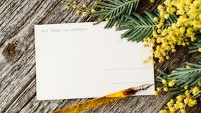 Rocznik pocztówki wyśmiewają up z żółtymi kwiatów mimosas i rocznika pióra atramentem na popielatym drewnianym tle Obrazy Stock