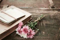 Rocznik powieść rezerwuje z bukietem kwiaty na starym drewnianym tle Fotografia Royalty Free