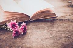Rocznik powieść rezerwuje z bukietem kwiaty na starym drewnianym tle Obraz Stock