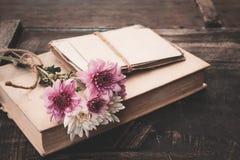 Rocznik powieść rezerwuje z bukietem kwiaty na starym drewnianym tle Zdjęcie Royalty Free