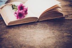 Rocznik powieść rezerwuje z bukietem kwiaty na starym drewnianym tle Zdjęcia Royalty Free