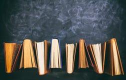 Rocznik rezerwuje pozycję na blackboard tle - odgórny widok Obraz Stock