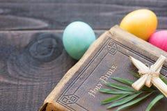 Rocznik Rzemienna biblia z trawa krzyżem, palma opuszcza na Ciemnym Nieociosanym drewno deski tle, Kolorowi Wielkanocni jajka obrazy royalty free