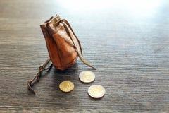 Rocznik rzemienna kieszonka na drewnianym biurku z euro monetami obok go, obraz stock