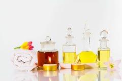 Rocznik stare butelki aromatyczni oleje z świeczkami, kwiatami i białym ręcznikiem na glansowanym bielu stole na białym tle, fotografia stock