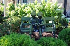 Rocznik statua dwa dziecka wśród hortensi kwitnie w ogródzie obrazy royalty free